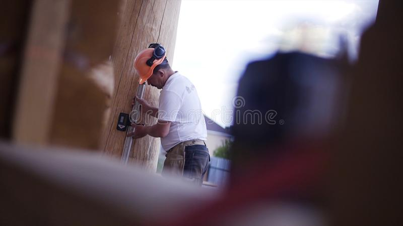 Working measures the height of the laser device. Clip. A young construction engineer makes room measurements with a royalty free stock image