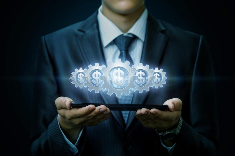 The working mechanism of cogwheels with currency units inside is hanging above the device in businessman`s hands . royalty free stock image