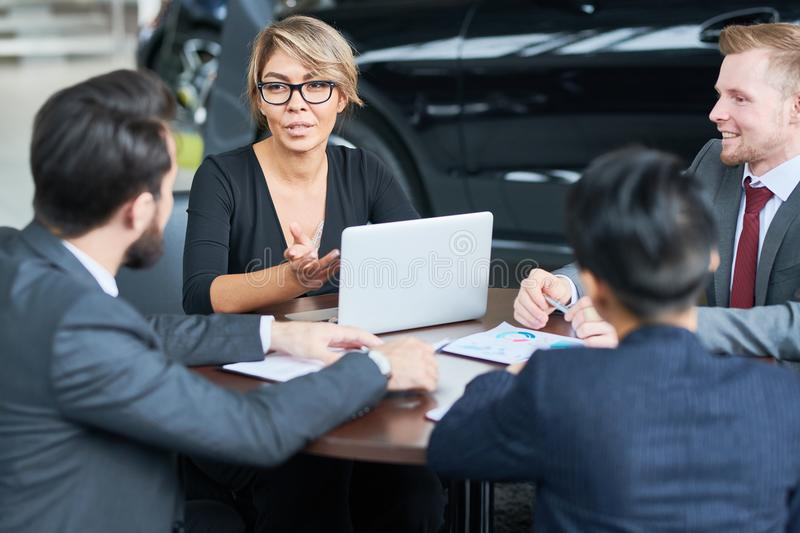 Working Meeting of Car Dealers. Multi-ethnic team of car dealers in formalwear gathered together at showroom and sharing ideas concerning sales growth stock images
