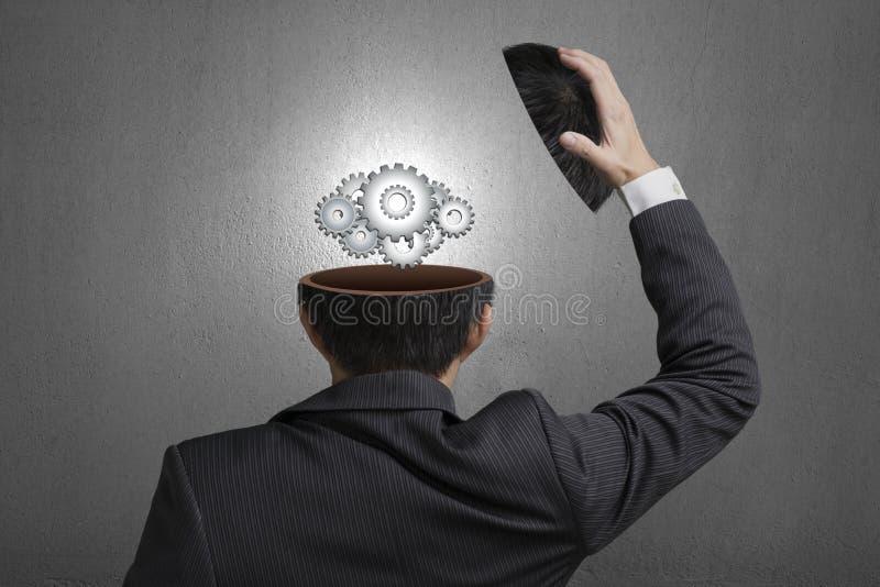 Working metal gears inside businessman head in gray concrete wall background stock photo