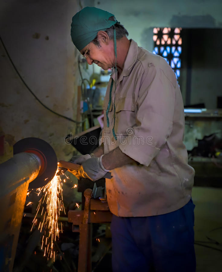 Working at a Metal Shop, Havana, Cuba. A man works on refining a piece of metal in a small shop in Havana, Cuba, with sparks flying from a wheel used to work on royalty free stock images
