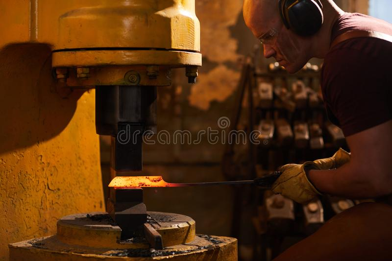 Working with metallurgical press machine. Concentrated bald blacksmith in ear protectors and safety goggles putting heated metal under press while working with stock images