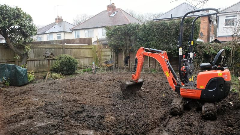 Working Micro Digger. A Micro Digger being used in a garden makeover to make way for a new lawn royalty free stock photos