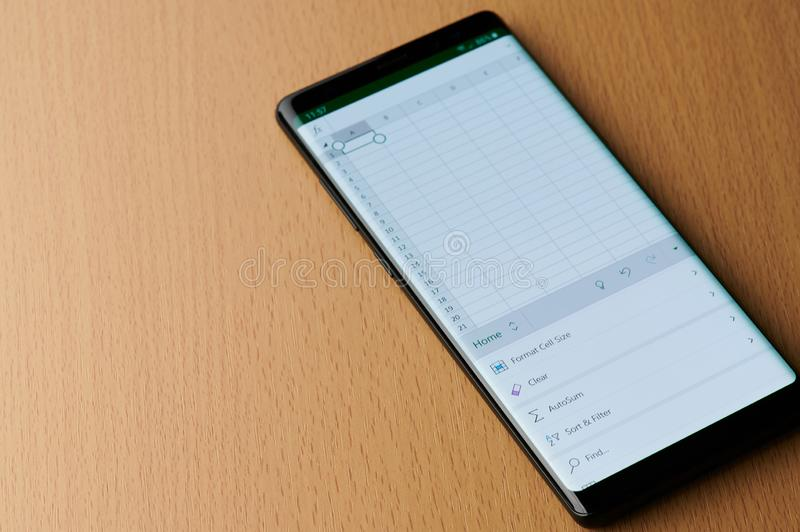Working in Microsoft excel. New york, USA - march 6, 2019: Working in Microsoft excel application on smartphone screen laying on wooden desk stock images
