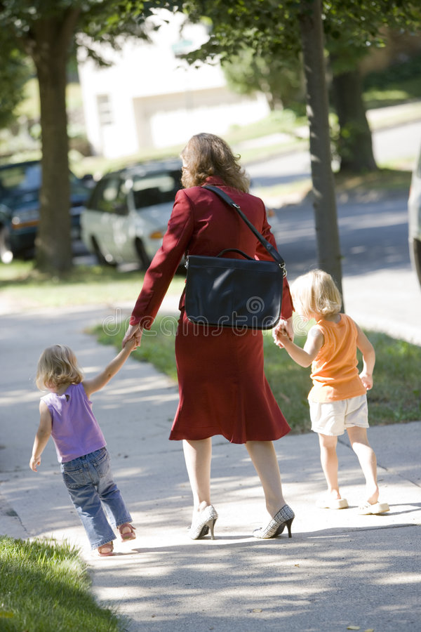Working mom bringing her kids to daycare. Professional woman walking her children to school or daycare stock images
