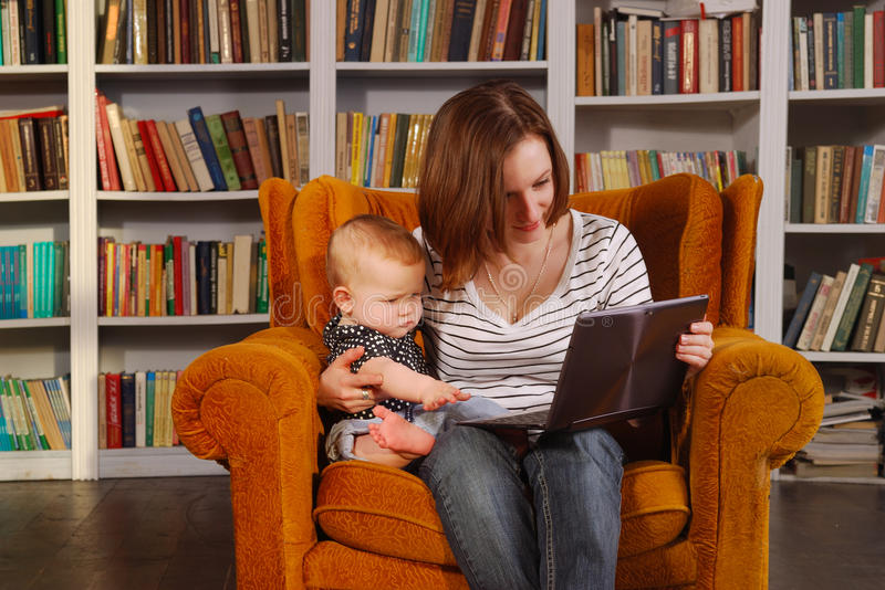 Working mom. Pretty young woman and her baby child are surfing internet with tablet transformer stock image