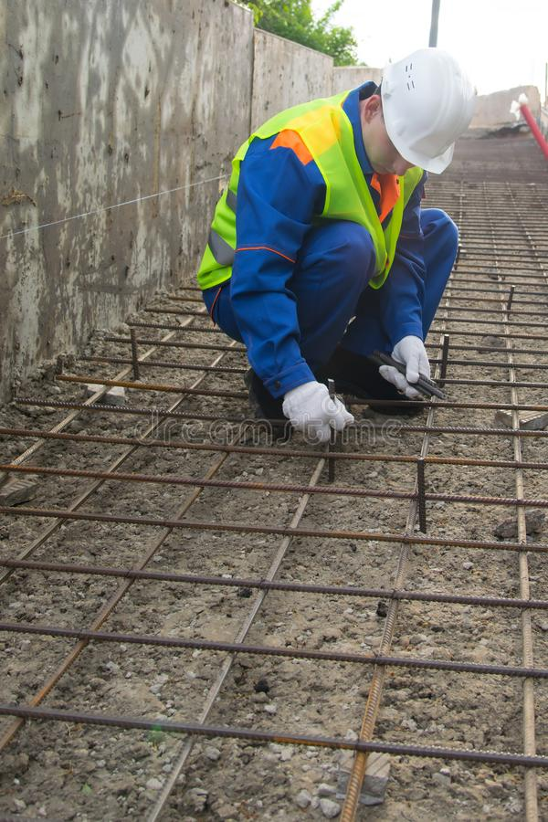 Working moments on the binding of reinforcement, before the preparation of concrete pouring, surface, working in blue uniform and royalty free stock photos