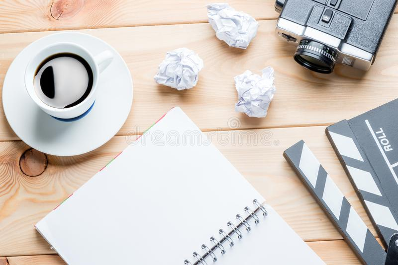 working moments of the writer - notepad, crumpled paper and video camera on wooden boards objects of the film industry royalty free stock photography