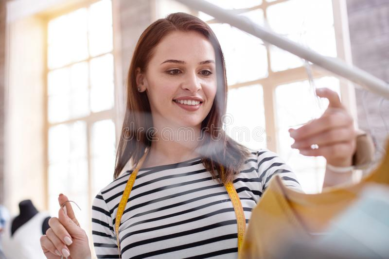 Optimistic female stylist organizing garments. Working mood. Low angle of energetic female stylist staring down while taking garments stock photography