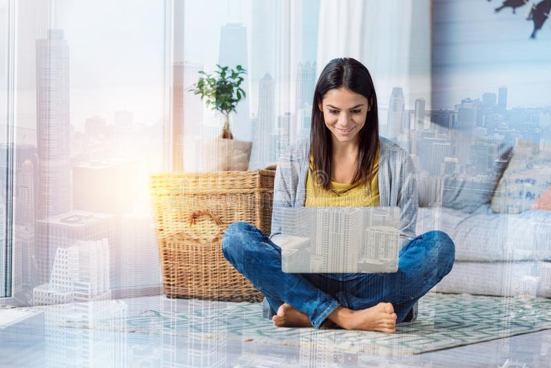 Cheerful young woman working while sitting at home royalty free stock photo