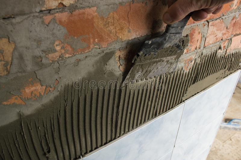 Working with mortar tiling a bathroom wall stock image