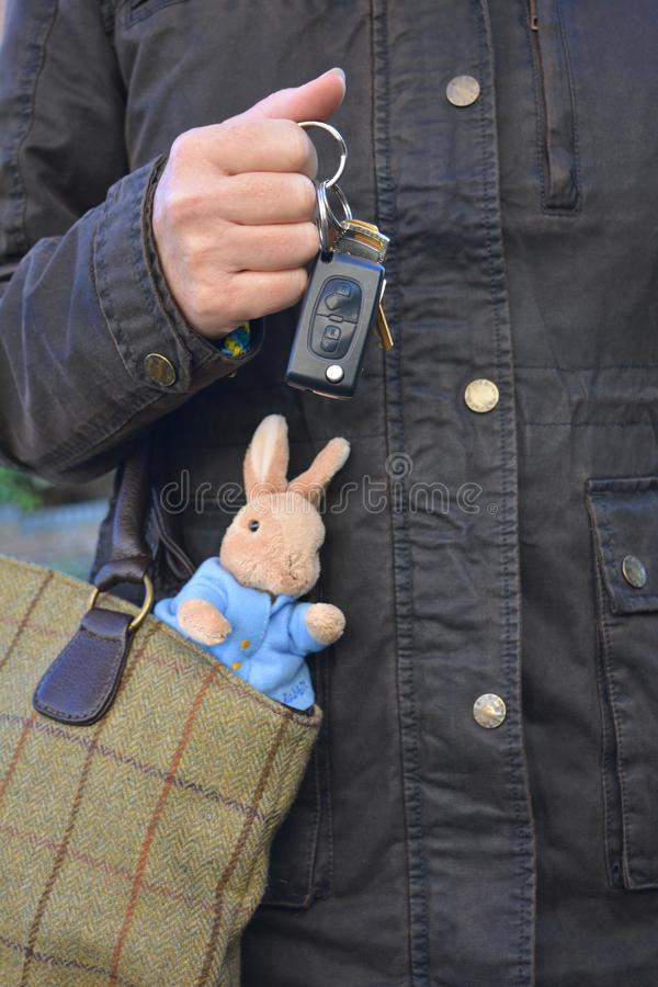 Working mother, with a child`s toy sticking out of her handbag. Working mother, mobile phone in hand and a child`s soft toy rabbit sticking out of her handbag royalty free stock image
