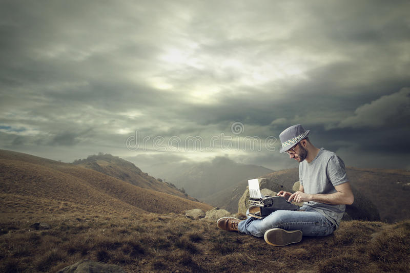 Working in the mountains. Man working at the computer sitting in the mountains royalty free stock images