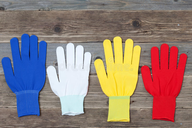 Working multicolored gloves. Four new working colored gloves on a old wood boards royalty free stock photos