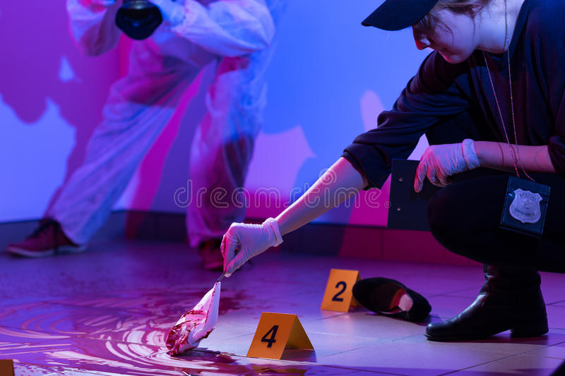 Working on a murder scene. Image of policewoman working on a murder scene royalty free stock image