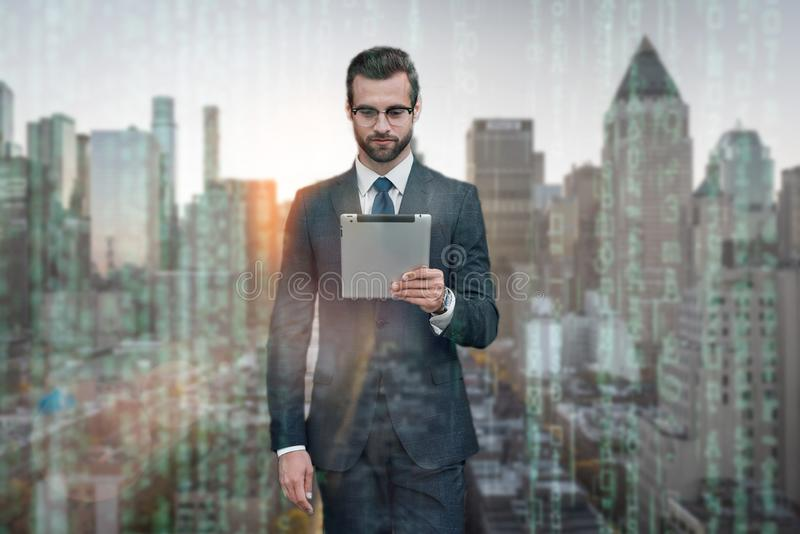 Working on new tablet. Confident and stylish businessman working on digital tablet while standing outdoors with modern royalty free stock photo