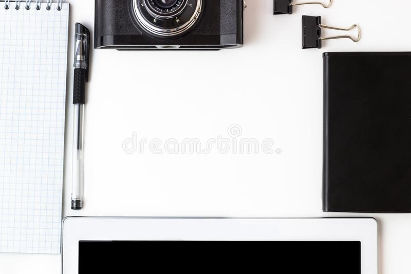 Working office space with a tablet, notepad, camera, external hard disk located on a white table, top view, flat lay stock photography