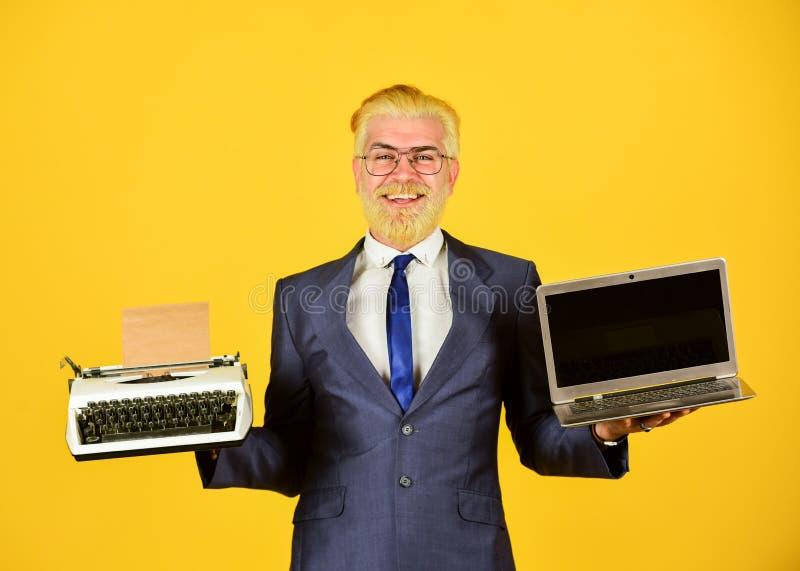 Working Online. vintage typewriter. successful businessman use retro typewriter and modern laptop. mature man dyed beard royalty free stock image
