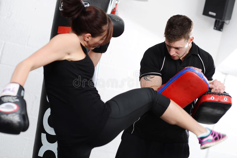 Working out, doing kicks on pads stock photo
