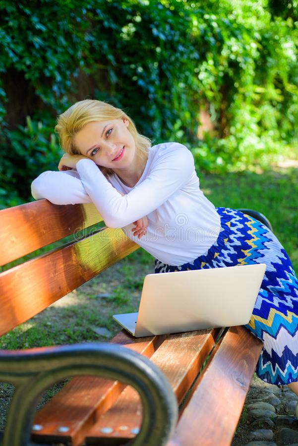 Working outdoors. Freelance lifestyle advantages. Casual and part time outdoor jobs. Girl sit bench with notebook. Woman. With laptop works in park enjoy green stock photography