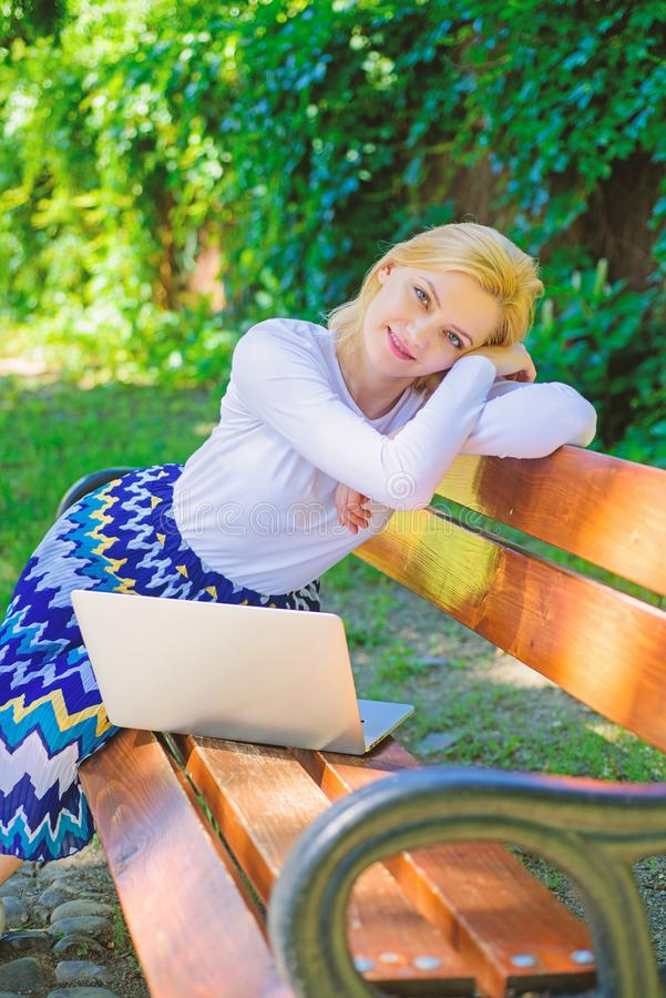 Working outdoors. Freelance lifestyle advantages. Casual and part time outdoor jobs. Girl sit bench with notebook. Woman. With laptop works in park enjoy green stock image