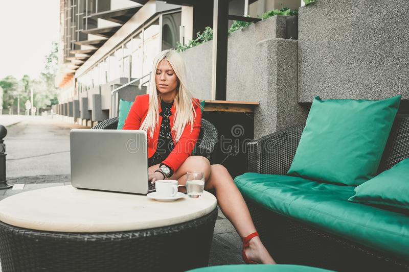 Pretty young business woman working on laptop in outdoor cafe royalty free stock photography
