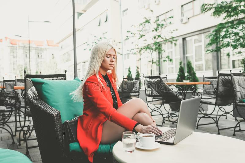Pretty young business woman working on laptop in outdoor cafe stock image