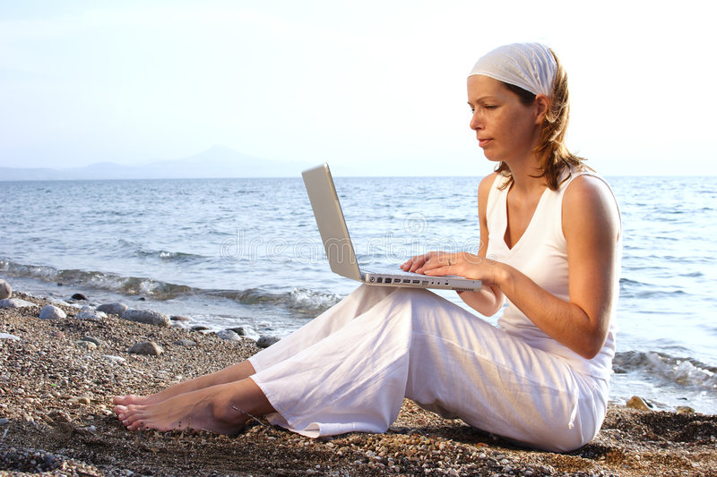 Working outside. Woman working on laptop at the beach