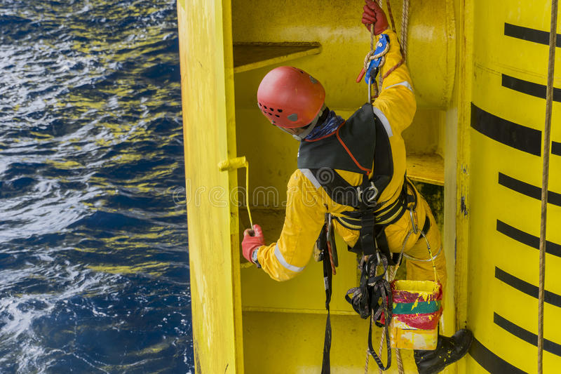 Oil and gas industrial occupational. Working overboard. A commercial abseiler complete with Personal Protective Equipment PPE hanging at oil and gas platform royalty free stock images