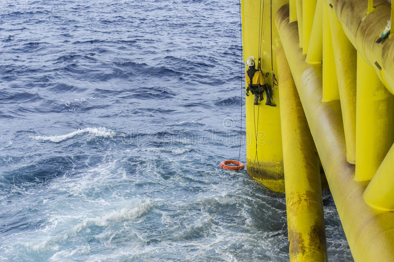 Oil and gas industrial occupational. Working overboard. A commercial abseiler complete with Personal Protective Equipment PPE hanging at oil and gas platform stock photos