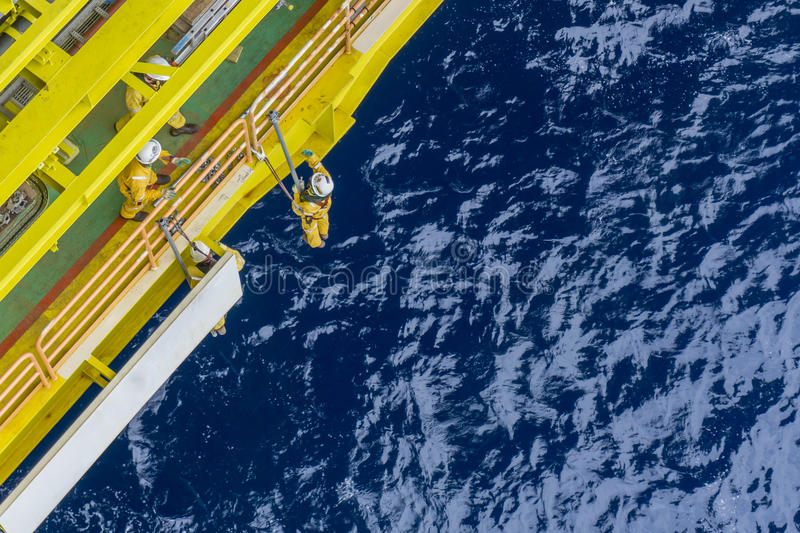 Oil and gas industrial occupational. Working overboard. A scaffolder team with fall arrester device and safety precaution hanging at the edge of oil and gas royalty free stock photography
