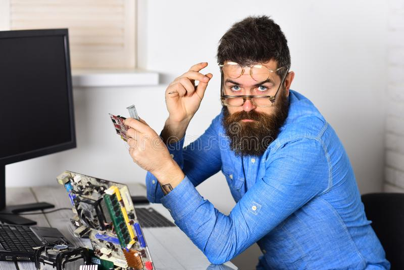 Working with passion. Assemblying of electronic devices. Bearded man repair circuit board. Engineer or technician at. Work. Bearded hipster works on fixing royalty free stock photography