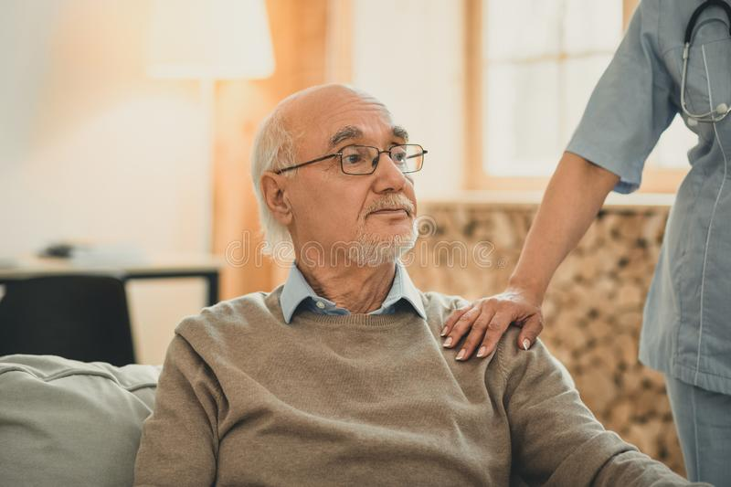 Kind doctor putting her hand on the shoulder of patient. Working with patient. Kind doctor putting her hand on the shoulder of old patient in calming gesture stock photo