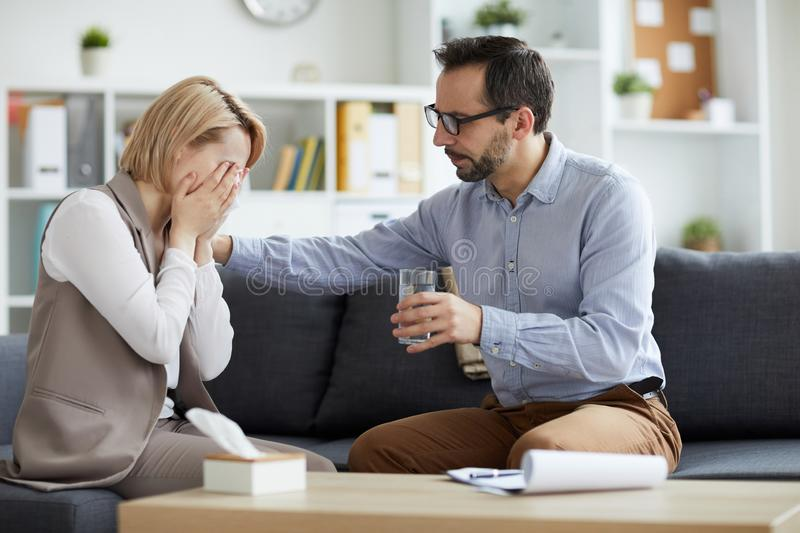 Working with patient. Professional counselor in eyeglasses offering glass of water to his crying patient while both sitting on couch royalty free stock images