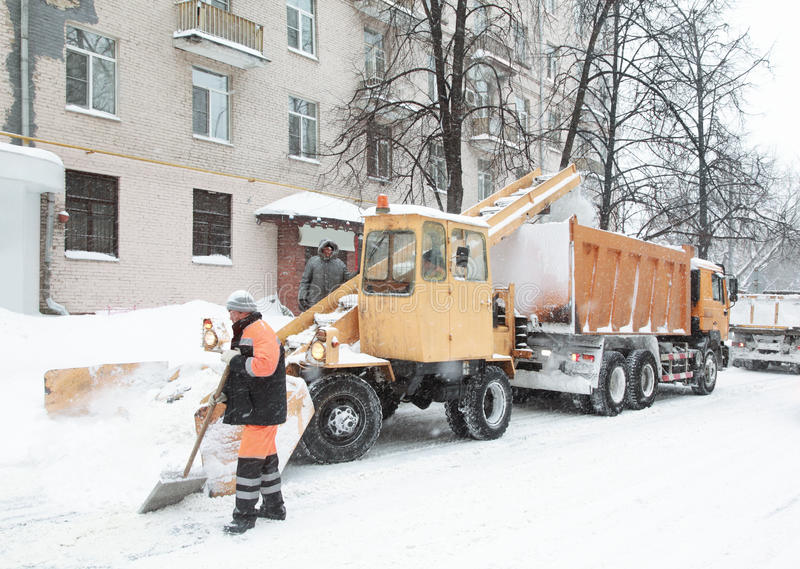 Working people clean the snow on street