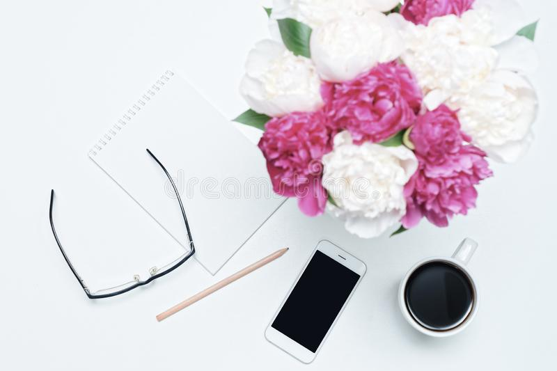 Working place with cup of coffee, mobile phone, paper, pen, glasses and white and pink peony flowers on white table background. royalty free stock photography