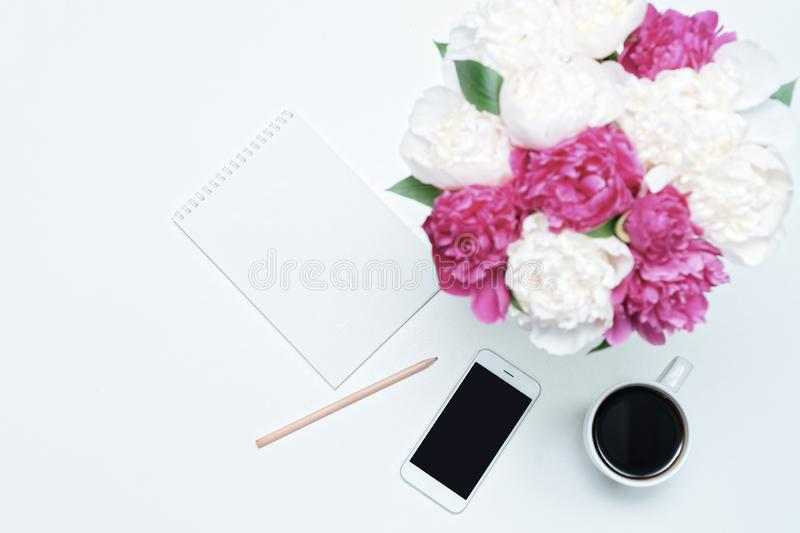 Working place with cup of coffee, mobile phone, paper, pen and white and pink peony flowers on white table background. Flat lay,. Top view royalty free stock photo