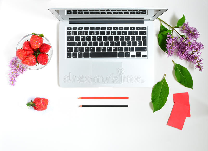 Working Place at Home or Office. Laptop, lilac flowers bouquet, strawberry and pencil on white background. Flat lay of working place stock image