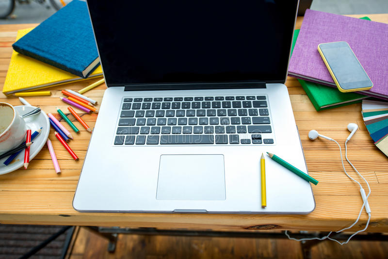 Working place. With laptop, colorful pencils, books, earphones and a cup of cooffee on the wooden table. Close up, top view royalty free stock photo