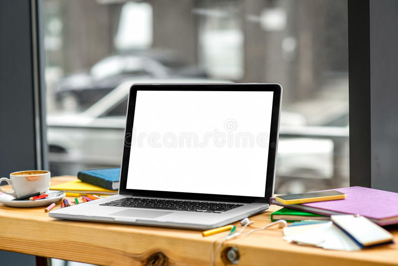 Working place. With laptop with white screen, colorful pencils, books, earphones and a cup of cooffee on the wooden table near the window stock photos