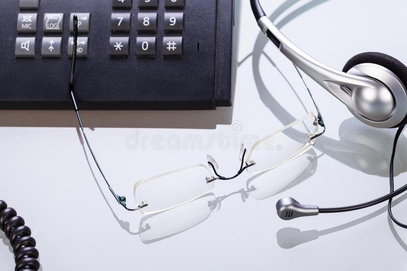 Working place office desk table headset glasses telephone royalty free stock photography