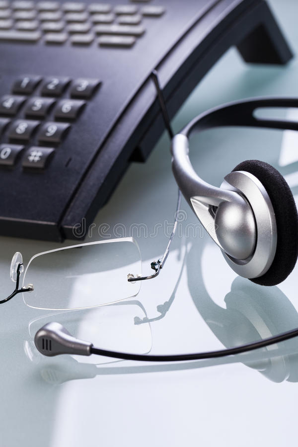 Working place office desk table headset glasses telephone. Objects business royalty free stock photography