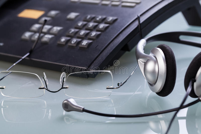 Working place office desk table headset glasses telephone. Objects business royalty free stock photos