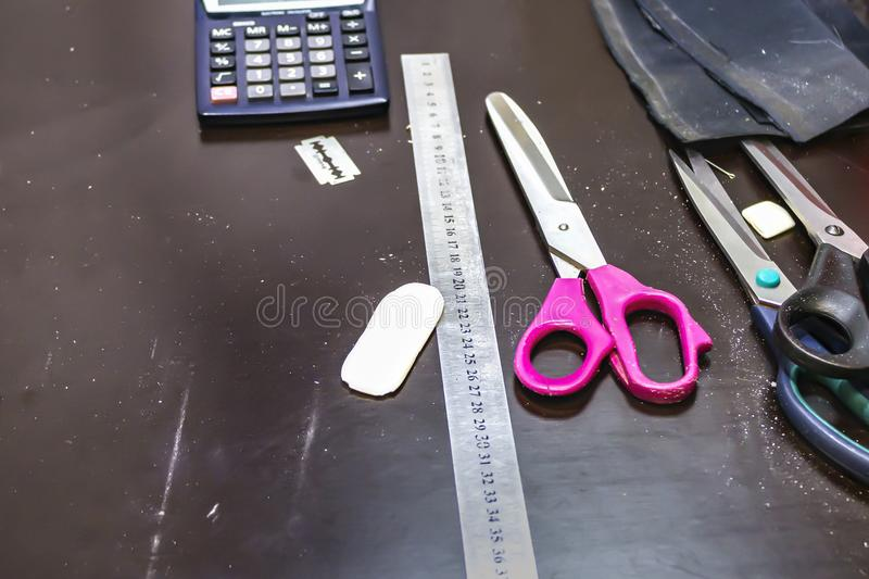 Working place of a seamstress. Ruler, scissors, calculator, chalk on the table stock image