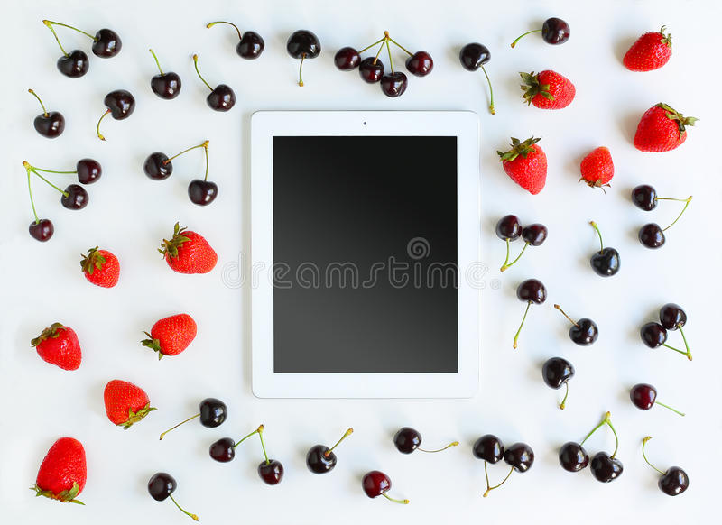 Working Place with Tablet. Tablet, cherry and strawberry on white background. Flat lay of working place. Mock up for art work royalty free stock images