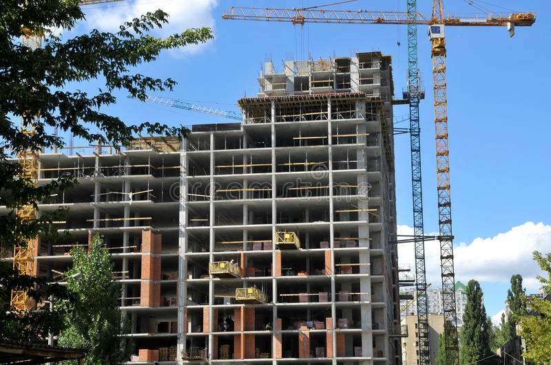 Working on place tall building under construction and cranes under stock photos