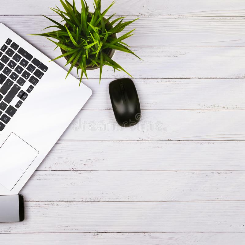 Working place on white wooden table with copy space. Laptop, mouse, phone, flower in a pot. Flat lay. Top view of blackboard. Office desk royalty free stock photos