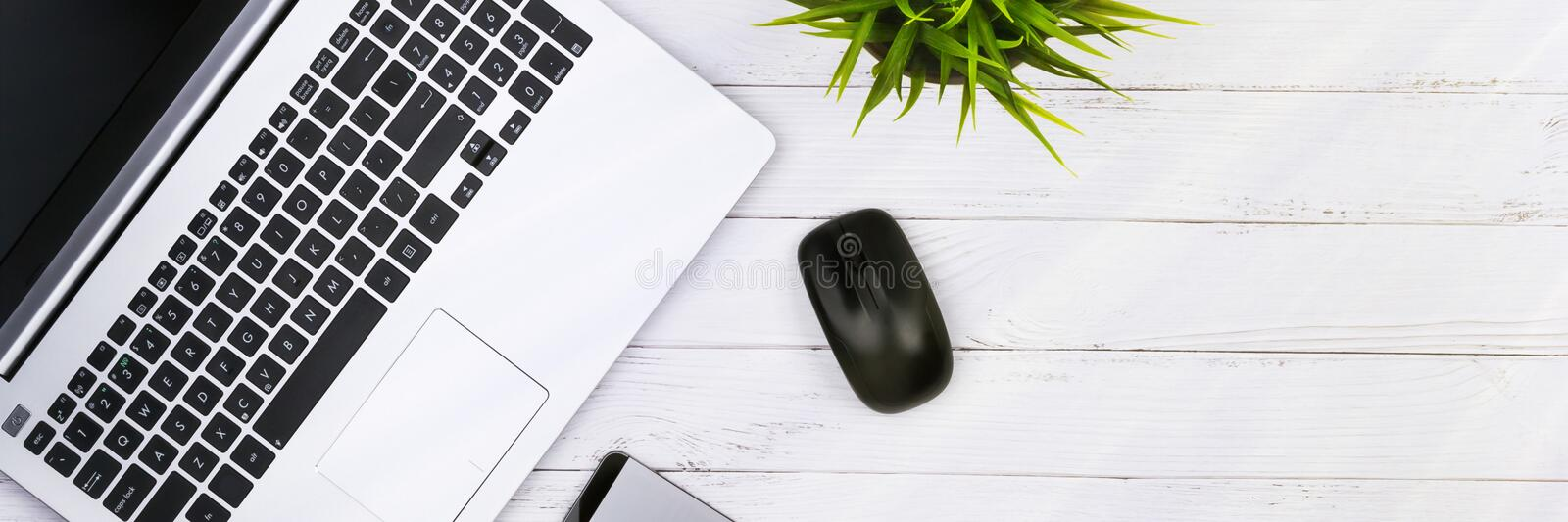 Working place on white wooden table with copy space. Laptop, mouse, phone, flower in a pot. Flat lay. Top view of blackboard. Office desk stock photography