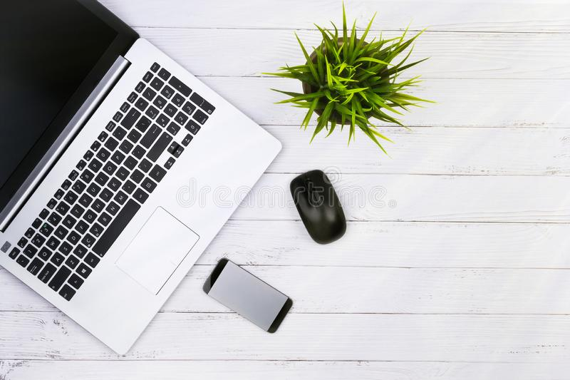 Working place on white wooden table with copy space. Laptop, mouse, phone, flower in a pot. Flat lay. Top view, the sun. `s rays from the side stock photo