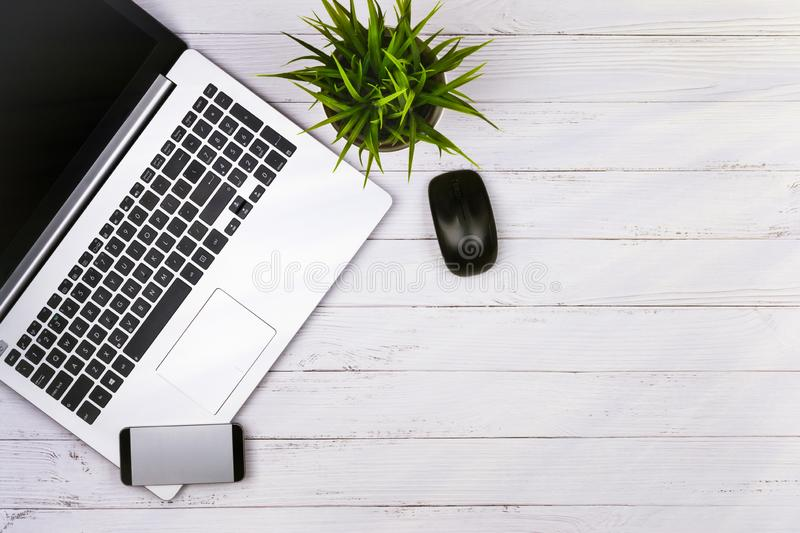 Working place on white wooden table with copy space. Laptop, mouse, phone, flower in a pot. Flat lay. Top view of. Blackboard office desk royalty free stock photography